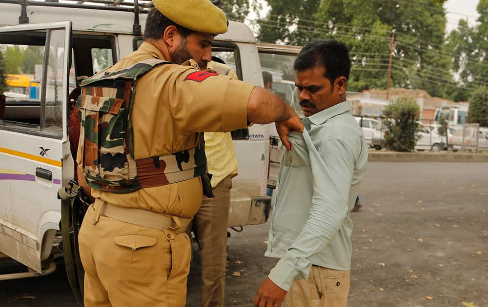 A policeman frisks a civilian at a busy road as part of enhanced security ahead of India's Independence Day in Srinagar.