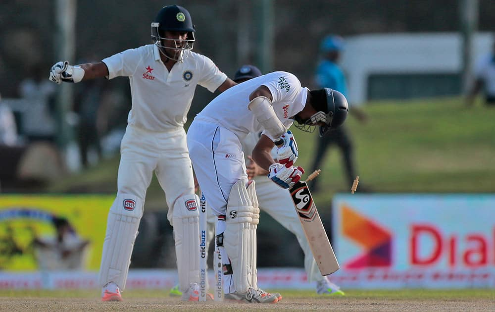 Sri Lankan batsman Dimuth Karunarathne looks back at his wicket after being bowled during the second day of the first test cricket match between Sri Lanka and India in Galle, Sri Lanka.