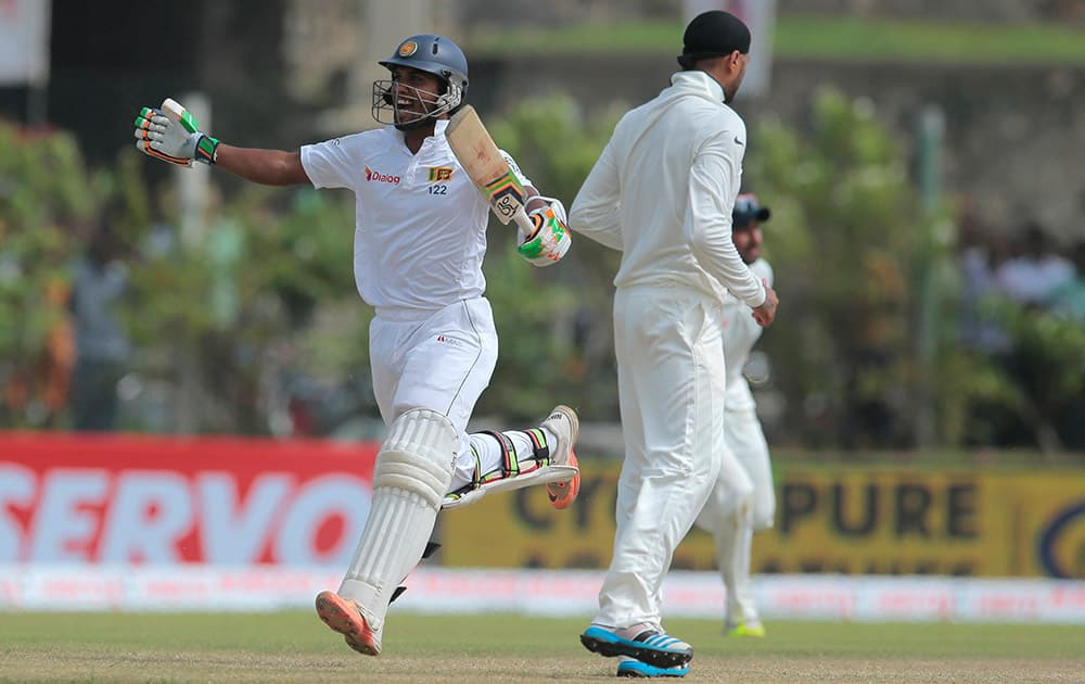 Sri Lanka's Dinesh Chandimal celebrates scoring a century during the third day of the first cricket test match between India and Sri Lanka in Galle, Sri Lanka.