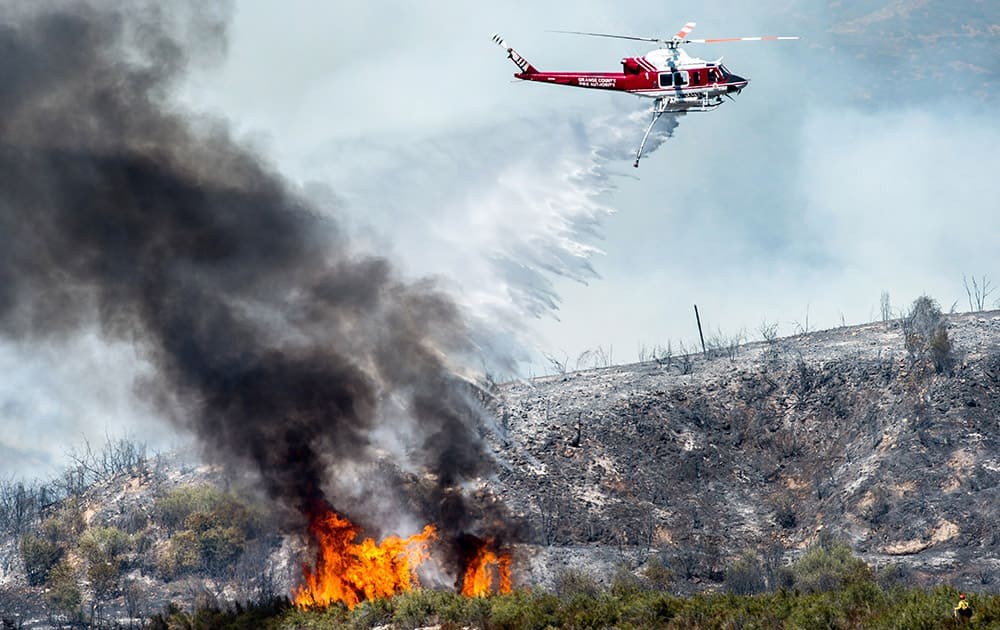 A helicopter makes a water drop on a wildfire in Angeles National Forest above Azusa, Calif.