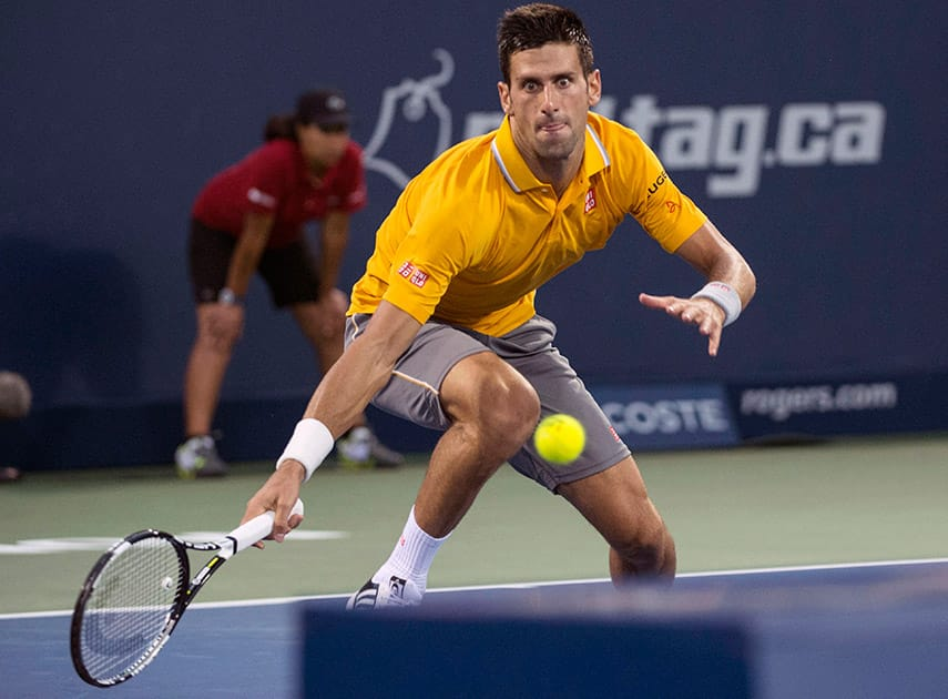 Novak Djokovic of Serbia runs for the ball to return to Ernests Gulbis of Latvia during the quarter finals at the Rogers Cup tennis tournament Friday Aug. 14, 2015 in Montreal.