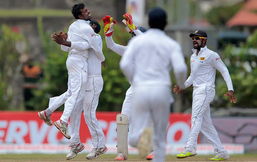 Tharindu Kaushal celebrates with teammates the dismissal of Virat Kohli during the fourth day of their first test cricket match in Galle, Sri Lanka. Sri Lanka won by 63 runs.