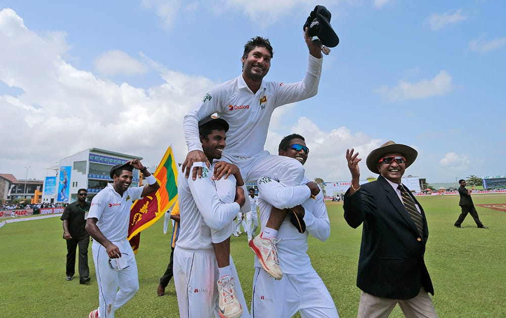 Sri Lankan team members carry Kumar Sangakkara on their shoulders as they walk around the field to celebrate their win over India by 63 runs in their first test cricket match in Galle, Sri Lanka.
