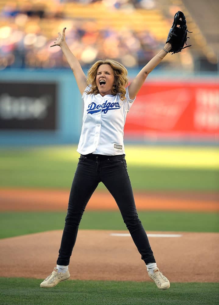 Actress Lea Thompson celebrates after throwing out the ceremonial first pitch prior to a baseball game between the Los Angeles Dodgers and the Cincinnati Reds in Los Angeles.