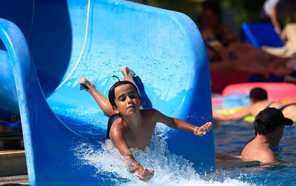 A child enjoys a water slide on a beach near the coastal town of Bodrum, Turkey.