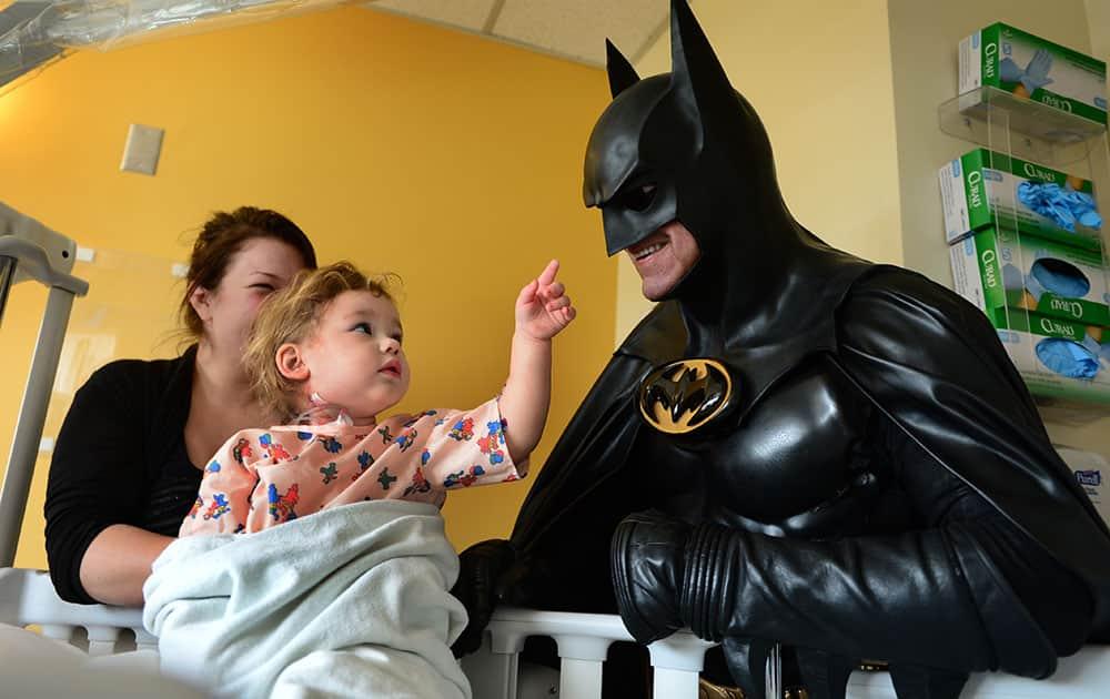 Leonard Robinson, dressed as Batman, visits Mattie Dillon on the pediatrics floor of Charleston Area Medical Center Women and Children's Hospital in Charleston, W.Va.