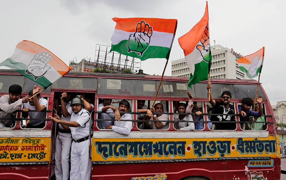 Congress party activists shout slogans from inside a bus after they were detained by policemen during a general strike in Kolkata.
