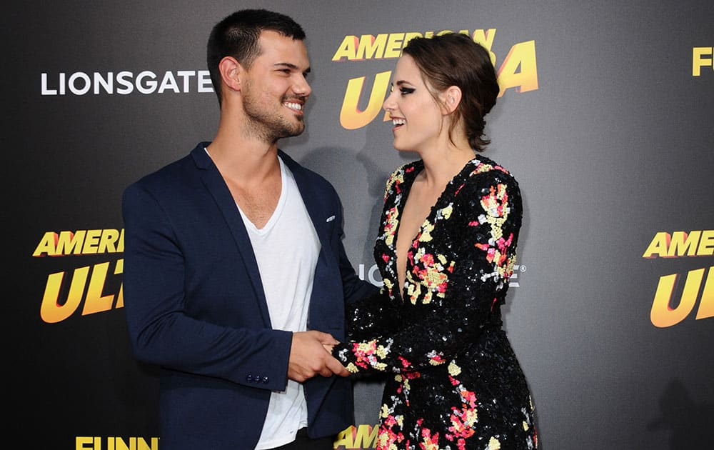 Taylor Lautner, left, and Kristen Stewart arrive at the Los Angeles premiere of