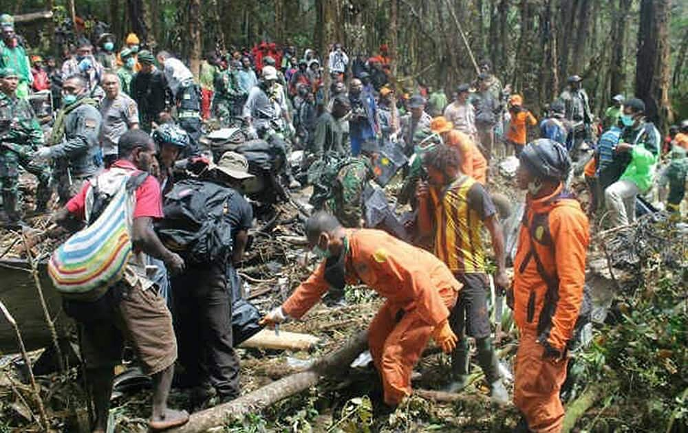 Rescuers work by the plane wreckage in Pegunungan Bintang, Papua province, Indonesia.