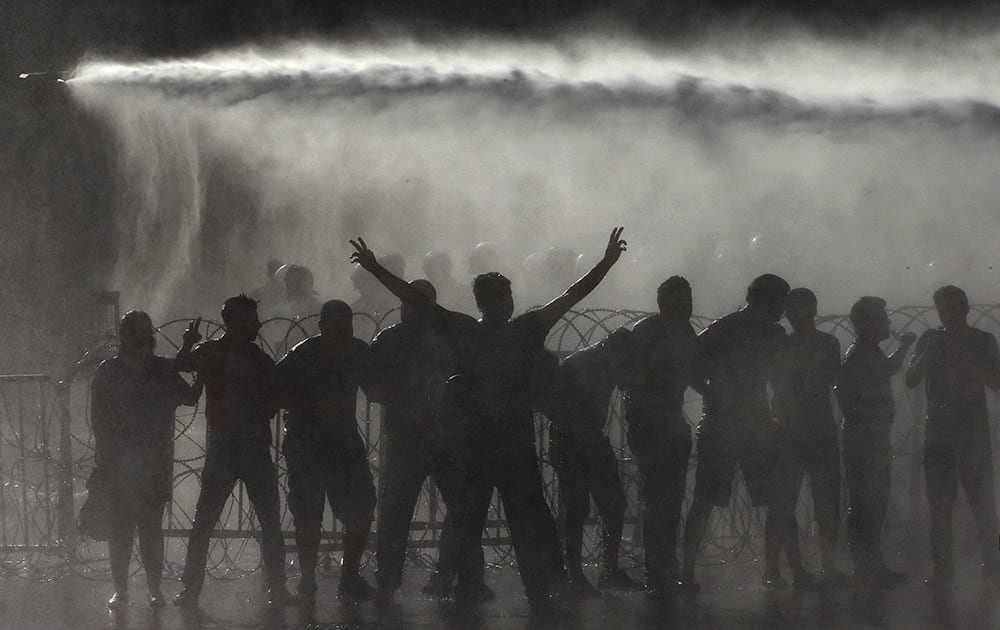 Lebanese activists are sprayed by riot police using water cannons, during a protest against the ongoing trash crisis, in front of the government house, in downtown Beirut, Lebanon.