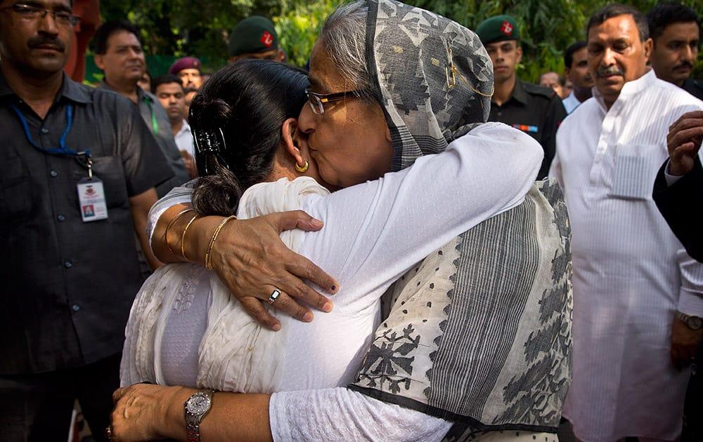 Bangladesh's Prime Minister Sheikh Hasina, right, embraces Sharmistha Mukherjee, daughter of Indian President Pranab Mukherjee, as she arrives to express her condolences on the demise of Mukherjee's wife Suvra Mukherjee in New Delhi.