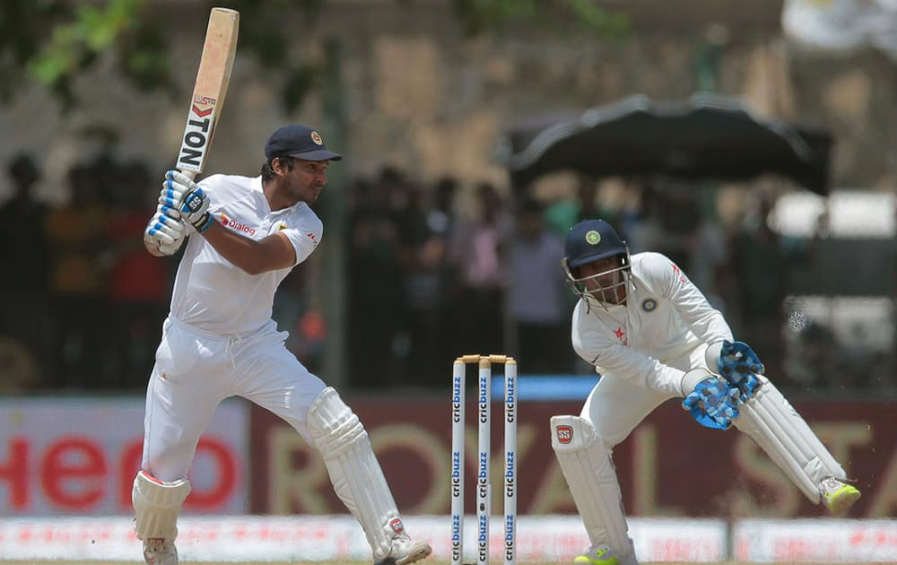 Sri Lanka's Kumar Sangakkara plays a shot as India's wicketkeeper Wriddhiman Saha watches during the third day of the first cricket test match between India and Sri Lanka in Galle, Sri Lanka.