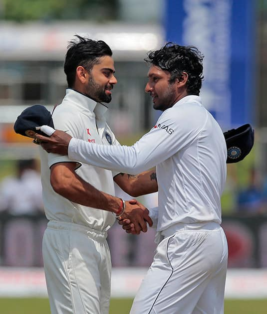 Sri Lanka's Kumar Sangakkara, right, shakes hands with India's captain Virat Kohli after their victory over India during the fourth day of their first test cricket match in Galle, Sri Lanka.