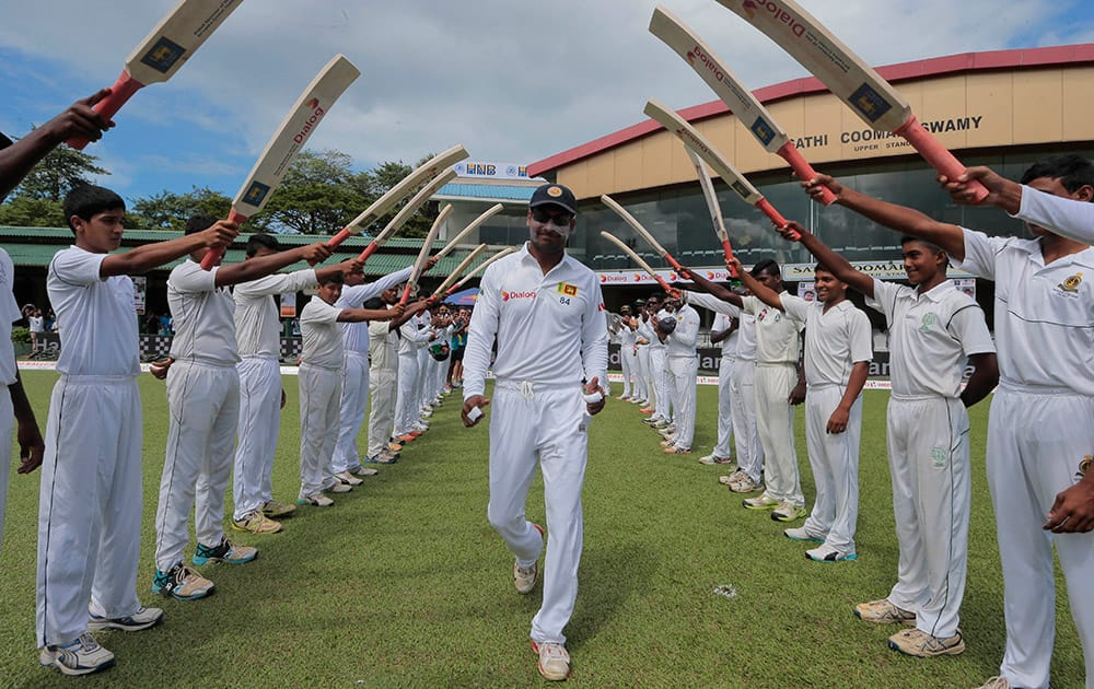 Sri Lankan cricketer Kumar Sangakkara, center, is greeted with an arch of bats as he enters the field for the last match of his test cricket career, the second test cricket match between Sri Lanka and India in Colombo.