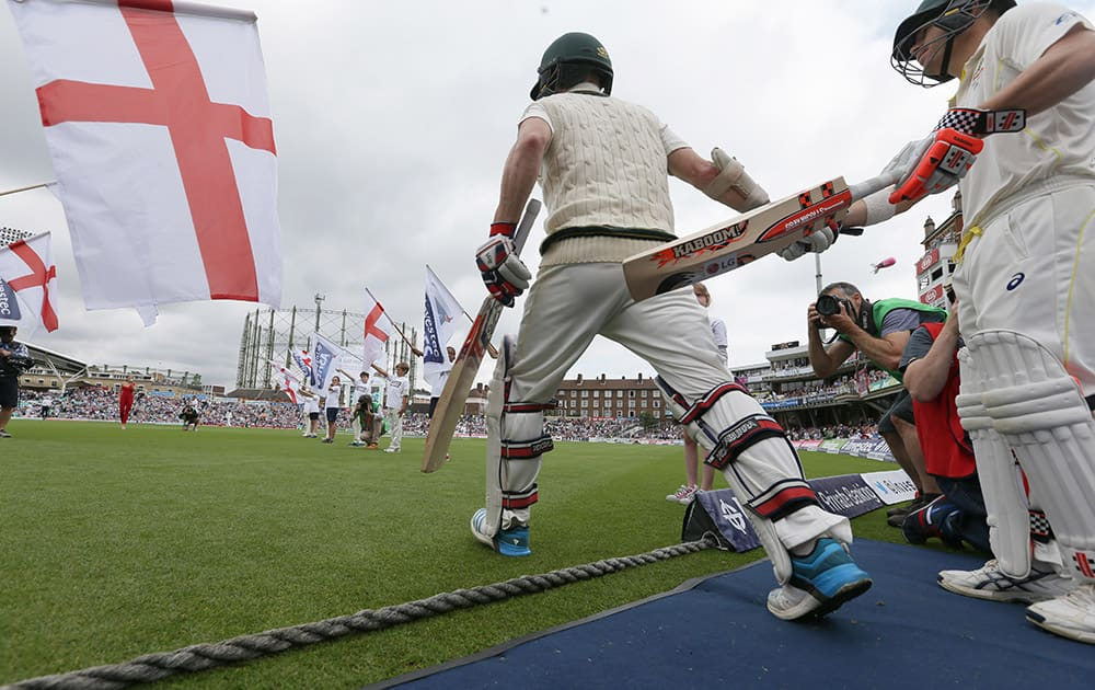 Australia's Chris Rogers and David Warner enter the ground on the first day of the fifth Ashes Test match between England and Australia, at the Oval cricket ground in London.