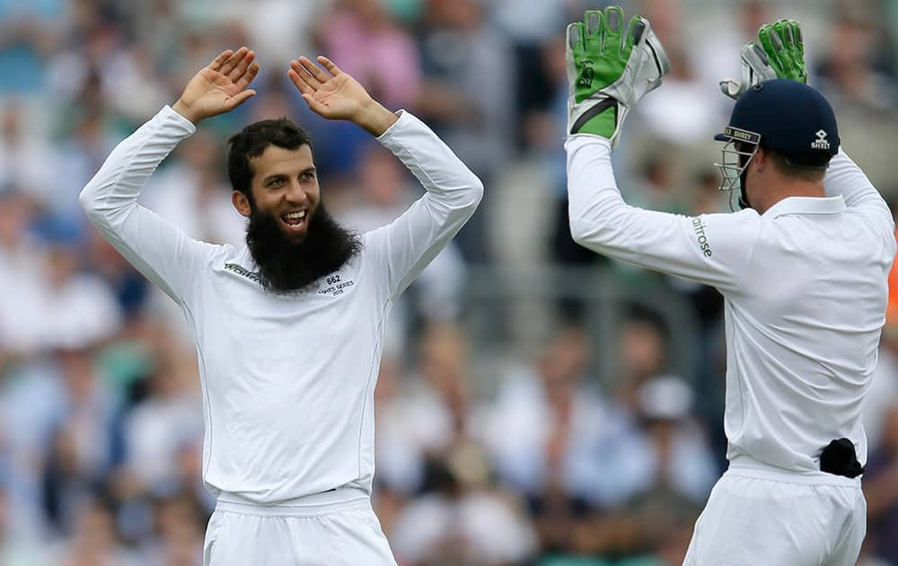 England's Moeen Ali celebrates taking the wicket of Australia's David Warner on the first day of the fifth Ashes Test match between England and Australia, at the Oval cricket ground in London.