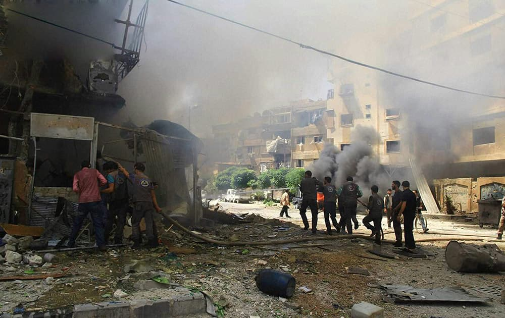 This photo provided by the Syrian anti-government activist group Douma Revolution, which has been authenticated based on its contents and other AP reporting, shows Syrian firefighters extinguishing a burning shop after a Syrian government airstrike, in Douma, a suburb of Damascus, Syria.