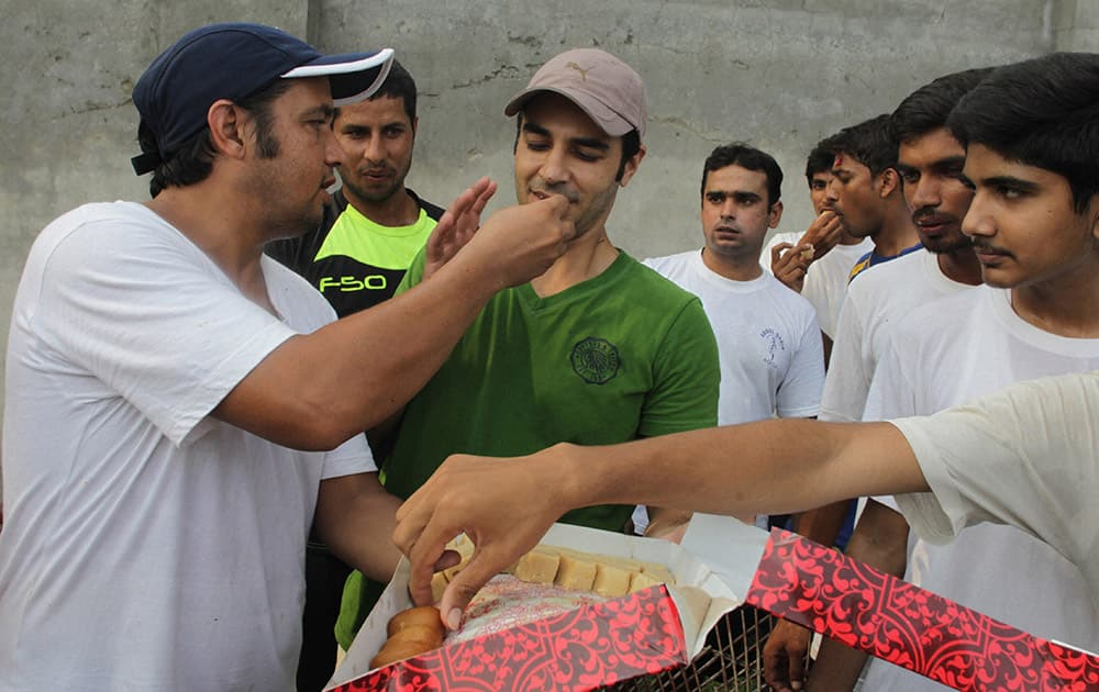 Pakistani cricket fans offer sweets to cricketer Salman Butt in Lahore, Pakistan.