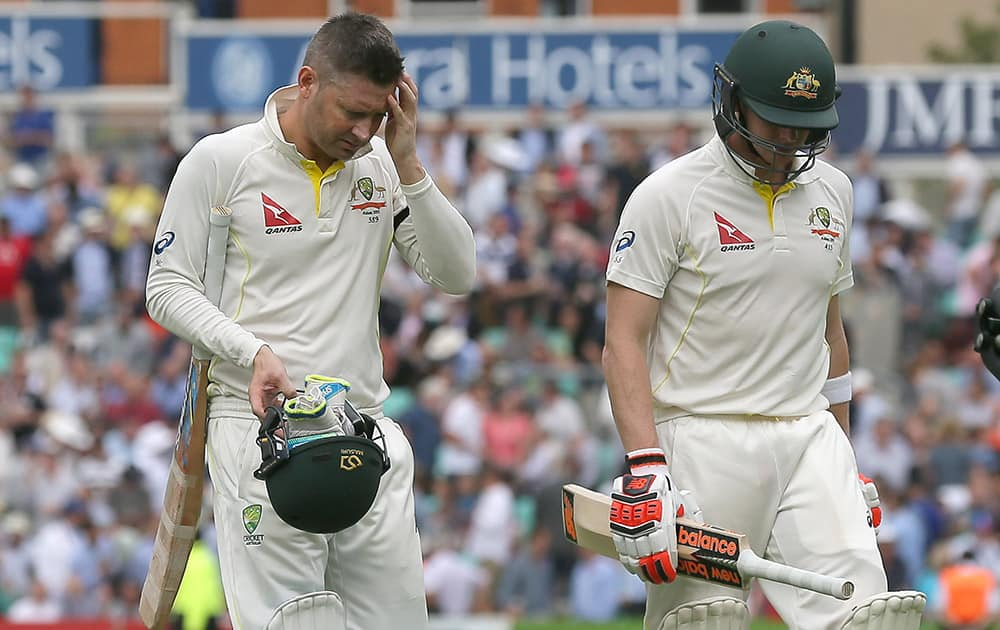 Australia's Michael Clarke, left, and Steven Smith leave the field as they break for tea on the first day of the fifth Ashes Test match between England and Australia, at the Oval cricket ground in London.