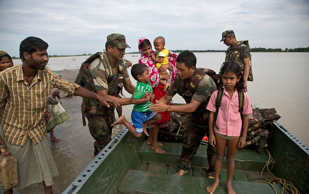 Indian army personnel transport flood-affected villagers to safer areas in a boat in Jaraguri village, about 160 kilometres (99 miles) west of Guwahati.