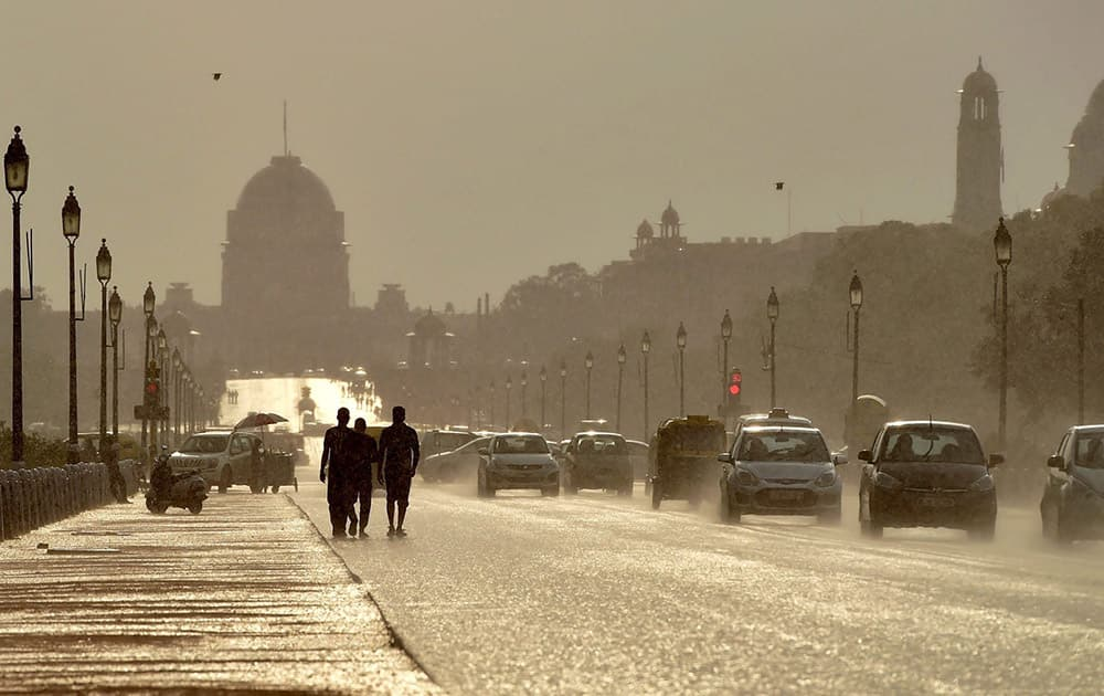 Vehicles move at Rajpath as it rains in New Delhi.
