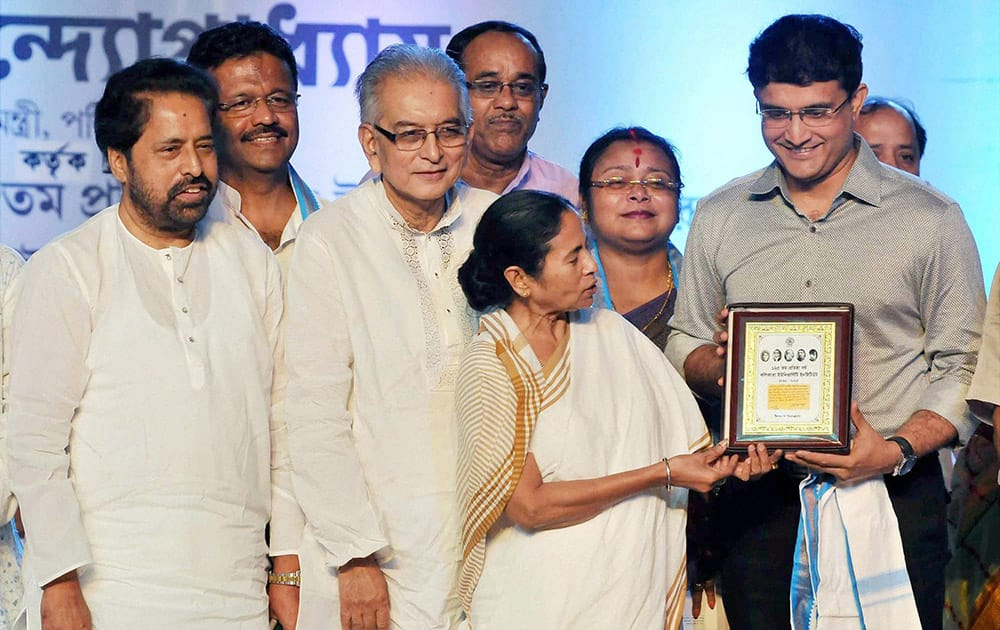 West Bengal Chief Minister Mamata Banerjee honours former cricketer Sourav Ganguly during the 125th foundation day of The Calcutta University Institute, in Kolkata.