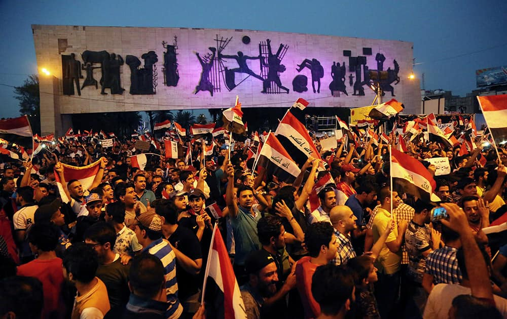 Protesters chant in support of Iraqi Prime Minister Haider al-Abadi as they carry national flags during a demonstration in Tahrir Square in Baghdad, Iraq.