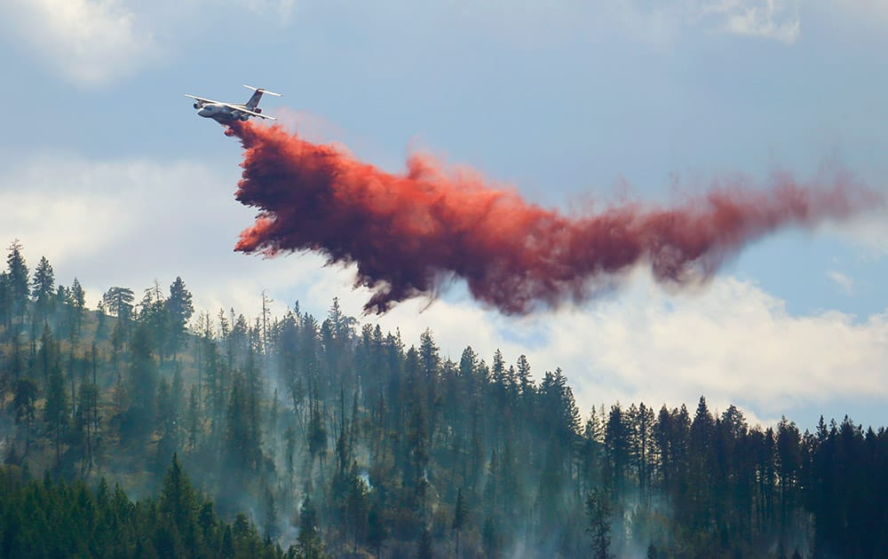 An airplane tanker drops fire retardant on a wildfire north of Twisp, Wash.