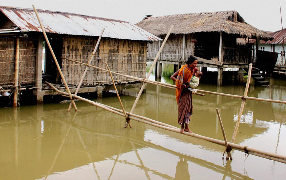 A woman uses a bamboo bridge to commute in a flood-hit village at Teok in Jorhat district of Assam.