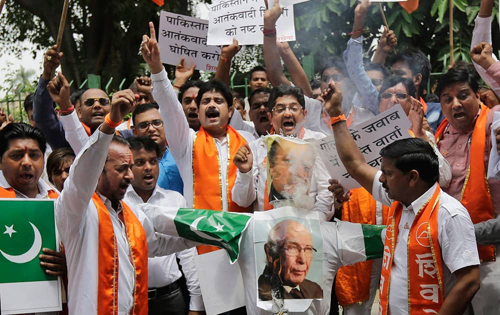 Hindu right-wing Shiv Sena activists burn an effigy and pictures of Pakistani Prime Minister Nawaz Sharif, top, and Pakistan's Prime Minister's Adviser on Foreign Affairs Sartaj Aziz during a protest in New Delhi.