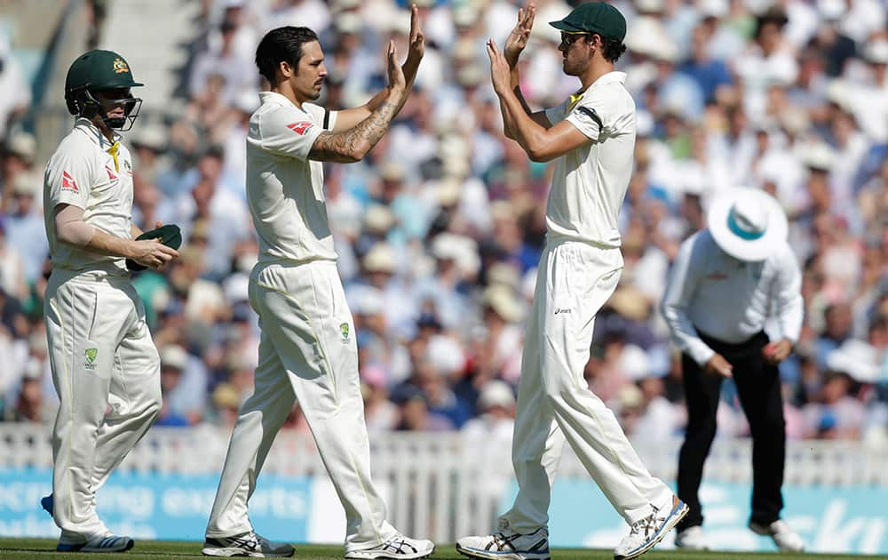 Australia's Mitchell Starc celebrates with teammate Australia's Mitchell Johnson after taking a catch to dismiss England's Mark Wood, off the bowling of Johnson, on the third day of the fifth Ashes cricket test between England and Australia at the Oval cricket ground in London.