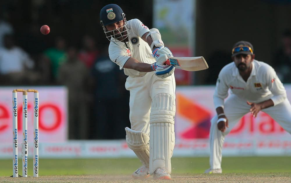 Ajinkya Rahane plays a shot as Lahiru Thirimanne watches during the third day's play of the second test cricket match between them in Colombo, Sri Lanka.