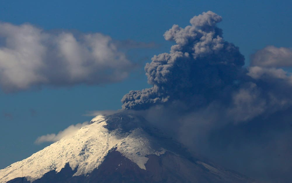 Ash and steam rise from the Cotopaxi volcano as seen from Quito, Ecuador.