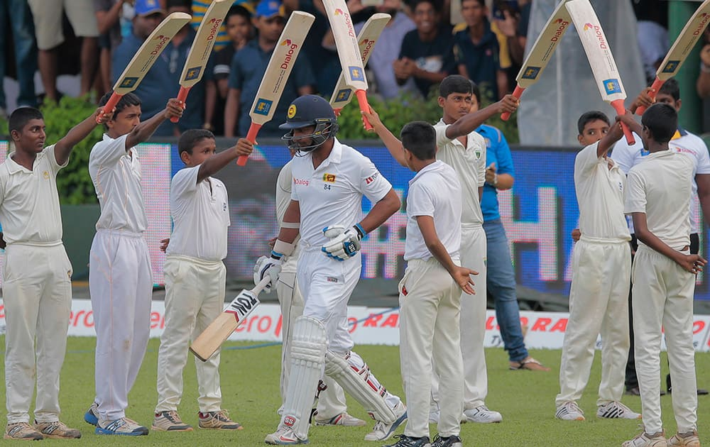 Sri Lanka national team player Kumar Sangakkara walks trough an arch of bats as he arrives in the field to bat in his final test innings during the fourth day's play of the second test cricket match between Sri Lanka and India in Colombo, Sri Lanka