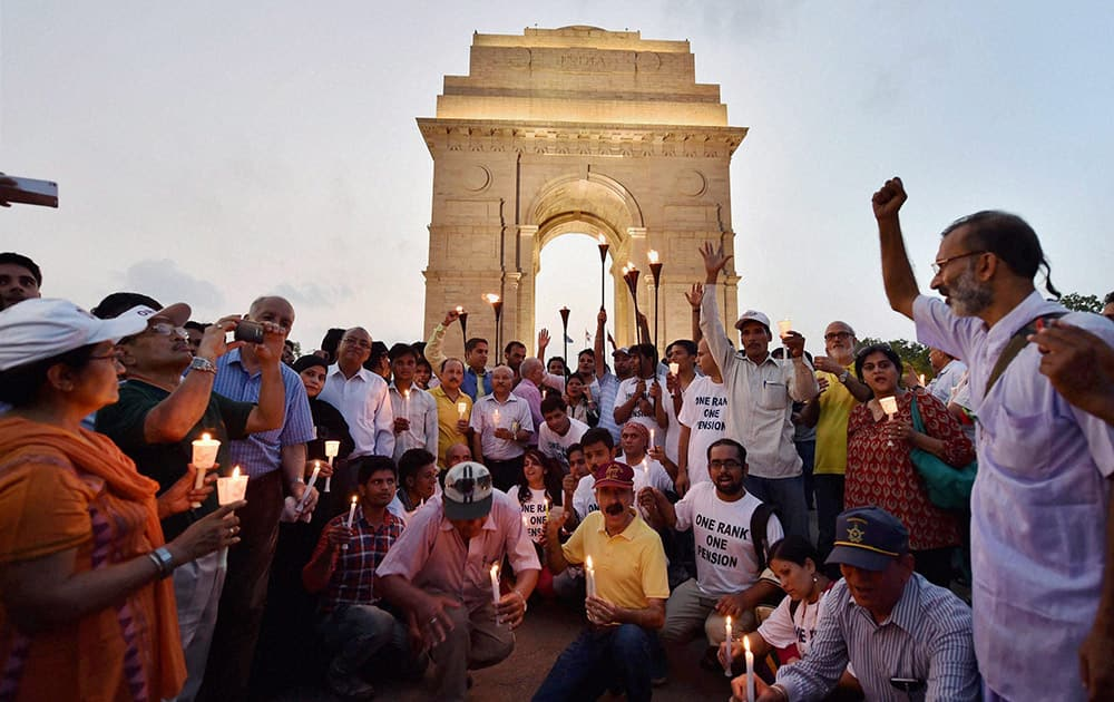 Ex-servicemen participate in the candle light march for One Rank One Pension at India Gate in New Delhi.