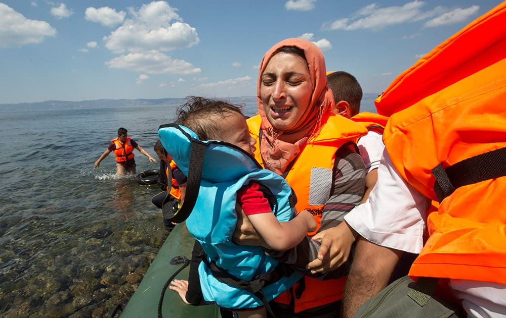 Syrian migrant mother holding her child breaks into tears as they reach the shore of Eftalou beach, 60 kilometers north of the port town of Mytilini after crossing the Aegean from Turkey on the southeastern Greek island of Lesbos, Greece.