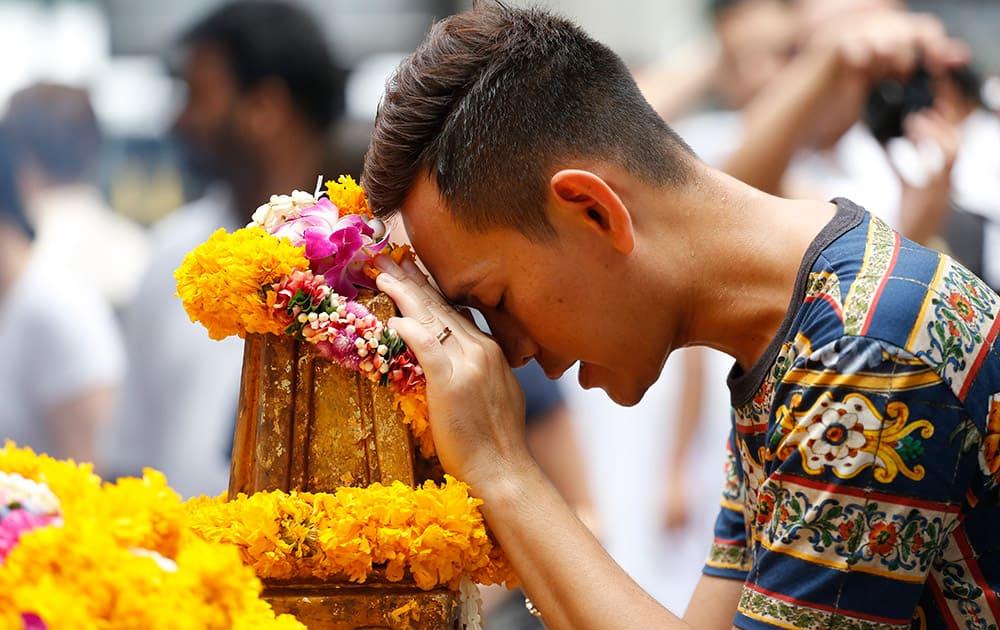 A man prays at the Erawan Shrine at Rajprasong intersection, the scene of last week's bombing, in Bangkok, Thailand.