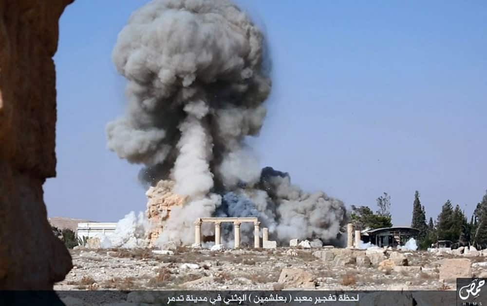 This undated photo released on a social media site used by Islamic State militants, which has been verified and is consistent with other AP reporting, shows smoke from the detonation of the 2,000-year-old temple of Baalshamin in Syria's ancient caravan city of Palmyra. A resident of the city said the temple was destroyed on Sunday, a month after the group's militants booby-trapped it with explosives. Arabic at bottom reads, 'The moment of detonation of the pagan Baalshamin temple in the city of Palmyra.'