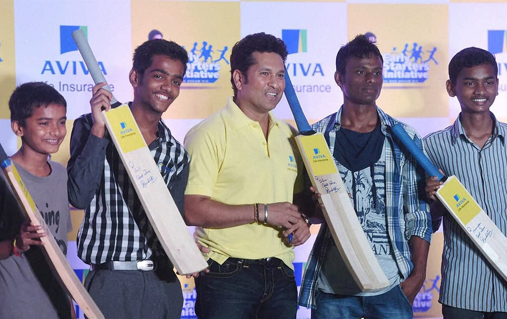 Cricket legend Sachin Tendulkar poses for a photo with the underprivileged children at an event of Avivas Early Starters imitative in Mumbai.