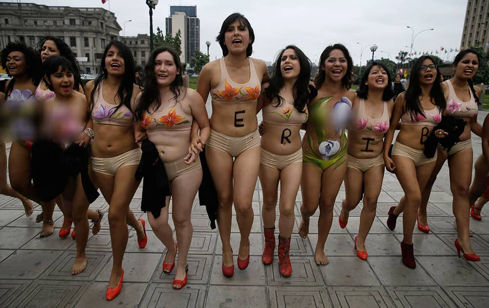 Women activists walk in Lima's downtown as they protest naked and in their undergarmets in Lima, Peru.