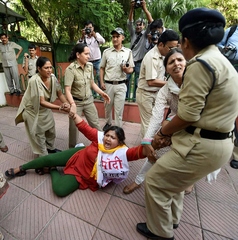 Police hold an activist during the protest by Youth Congress workers against hike in the prices of vegetables, in New Delhi.