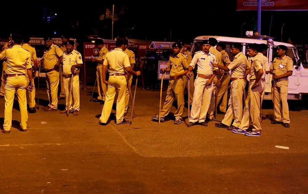 Policemen patrol on a street to nab people damaging vehicles after the arrest of Hardik Patel, convener of Patidar Anamat Andolan Samiti, in Ahmedabad.