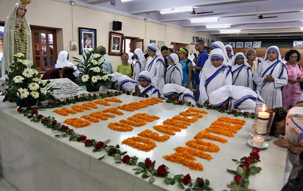 Nuns of the Missionaries of Charity pray beside the tomb of Mother Teresa during a mass on her birth anniversary in Kolkata, India.