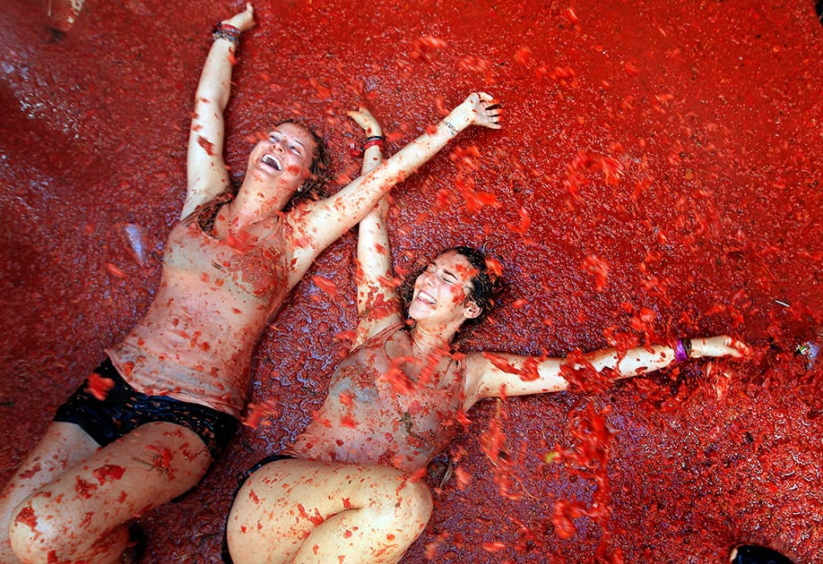 Two woman lie in a puddle of squashed tomatoes during the annual 'tomatina' tomato fight fiesta, in the village of Bunol, 50 kilometers outside Valencia, Spain.