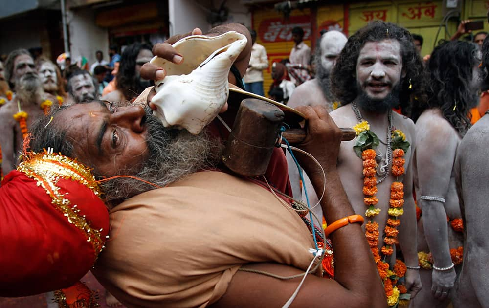 A Naga sadhu, or naked Hindu holy man, blows into a conch shell as he participates in a procession during Kumbh Mela, or Pitcher festival, at Trimbakeshwar in Nasik, India.
