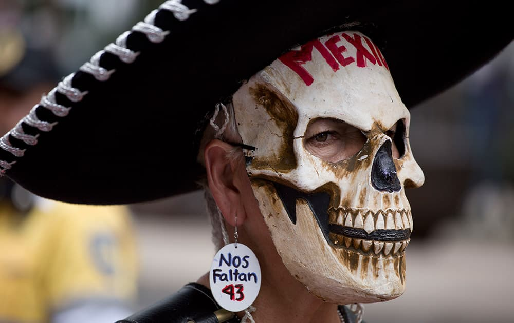 A demonstrator wears a Mexican Charro hat, a skull mask and an earring with text that reads in Spanish