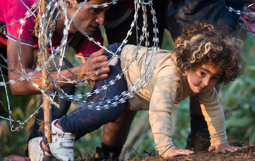 A refugee girl moves under barbed wire as she crosses from Serbia to Hungary, in Roszke.