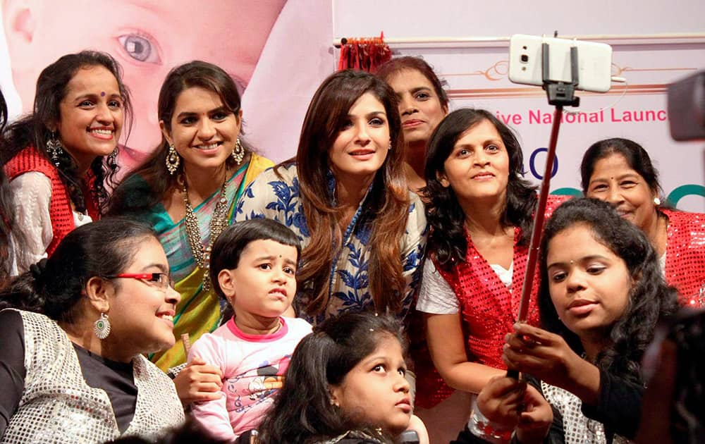 Ravina Tandon and BJP leader Shaina N C taking selfies with special children at the launch of Spina Bifida (Birth Defect) Awareness Campaign in Mumbai.