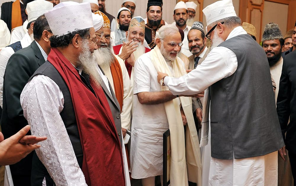 Prime Minister Narendra Modi is presented a scarf as he meets with a delegation of Sufi Scholars at PM House in New Delhi.