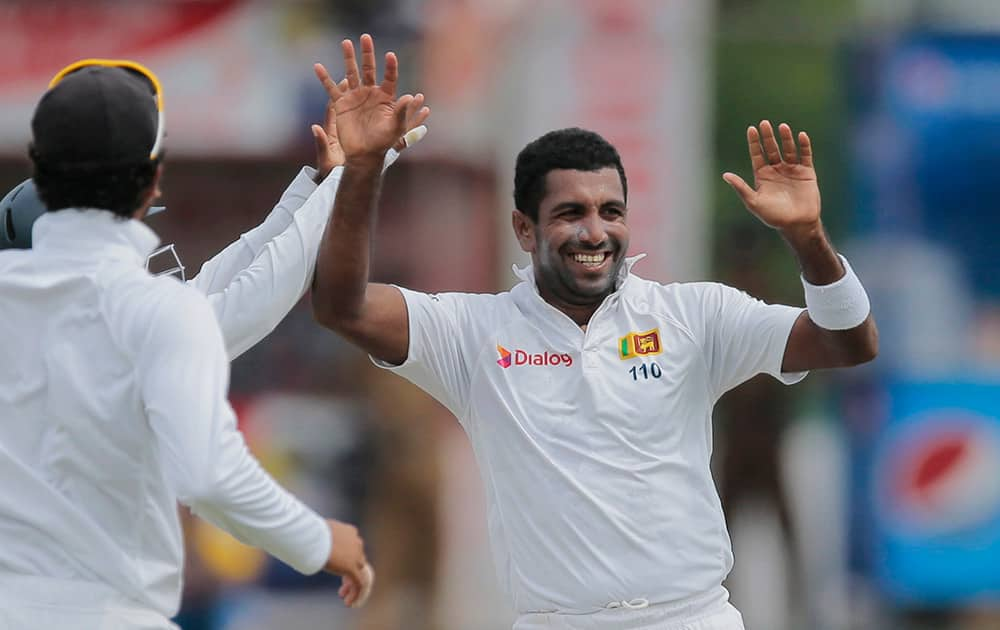 Sri Lanka's Dhammika Prasad celebrates the dismissal of India's Lokesh Rahul with his team mates on the day one of the third test cricket match in Colombo, Sri Lanka.